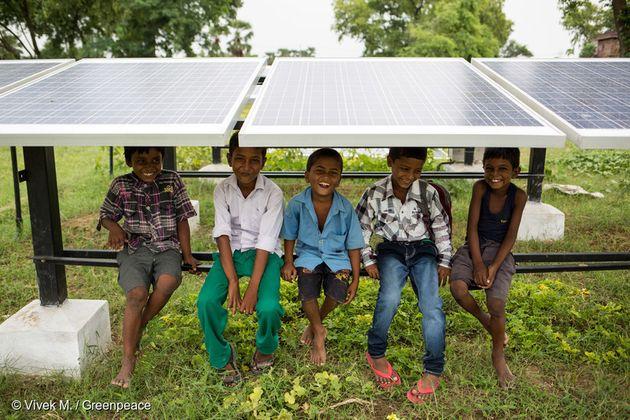 인도 Dharnai 마을의 어린이들이 태양광 패널 아래에 앉아 웃고 있다. 태양광 패널에서 생산된 전력은 마이크로 그리드를 통해 마을에 공급되고