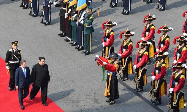Moon walks Kim alonga red carpet into South Korean territory, where school children placed flowers...