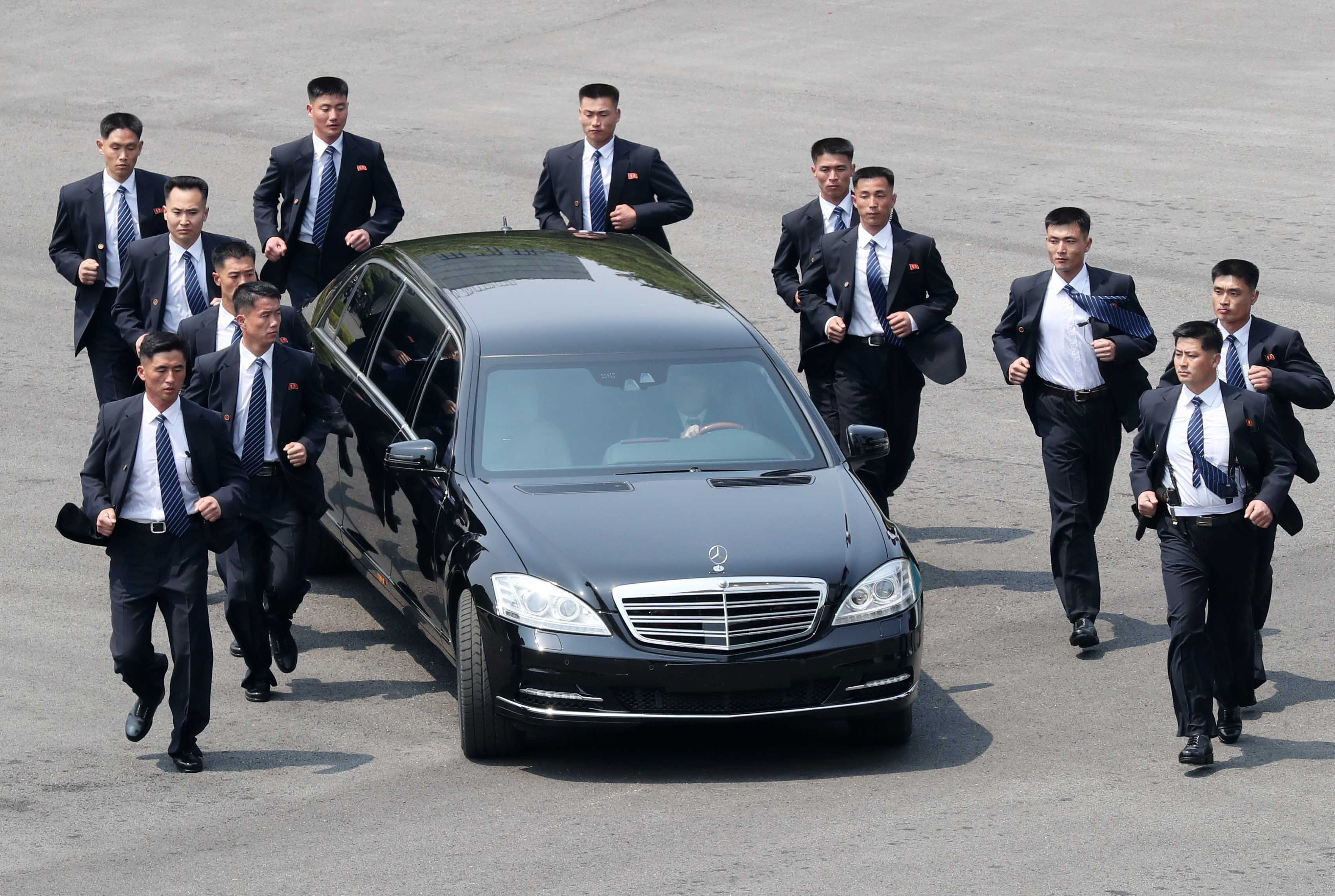 Kim Jong-Un's 'Strangely Hypnotic' Security Detail Steals The Show With 12-Man Synchronised Limo