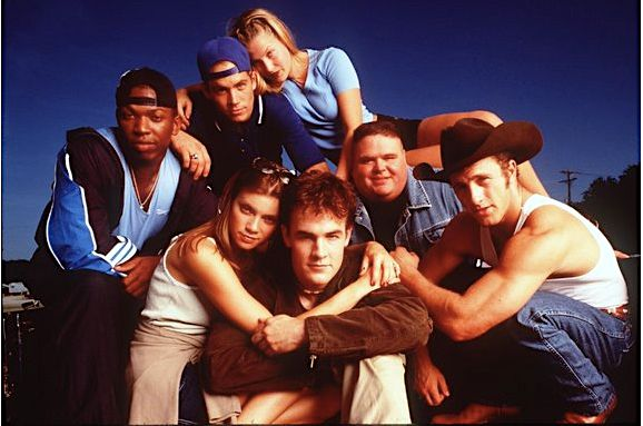 "Ali Larter (top) and Amy Smart with James Van Der Beek castmates in 1999's ""Varsity Blues."""