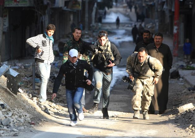Journalists run for cover in a street in Aleppo.