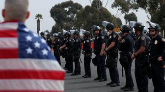 A large police presence watches over protesters and supporters during the visit of U.S. President Donald Trump to view border wall prototypes in San Diego, California, U.S., March 13, 2018. REUTERS/Mike Blake