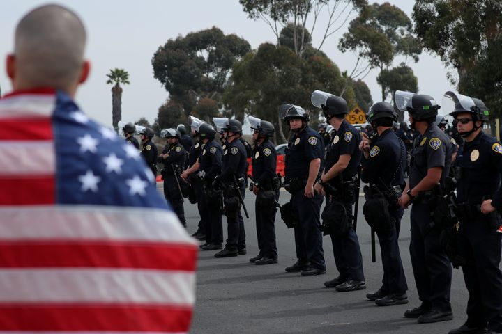 A large police presence watches over protesters and supporters during a visit by President Donald Trump to view border w