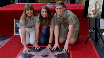 (L-R) Conservationists and TV personalities Terri Irwin, Bindi Irwin and Robert Irwin touch the newly unveiled star of Steve Irwin, who was honored posthumously with a Star on the Hollywood Walk of Fame in Hollywood, California on April 26, 2018. (Photo by Mark RALSTON / AFP)        (Photo credit should read MARK RALSTON/AFP/Getty Images)