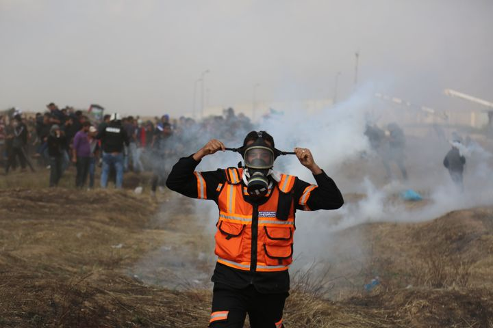 Tear gas canisters are fired by Israeli troops at Palestinian demonstrators during clashes at a protest demanding the right t