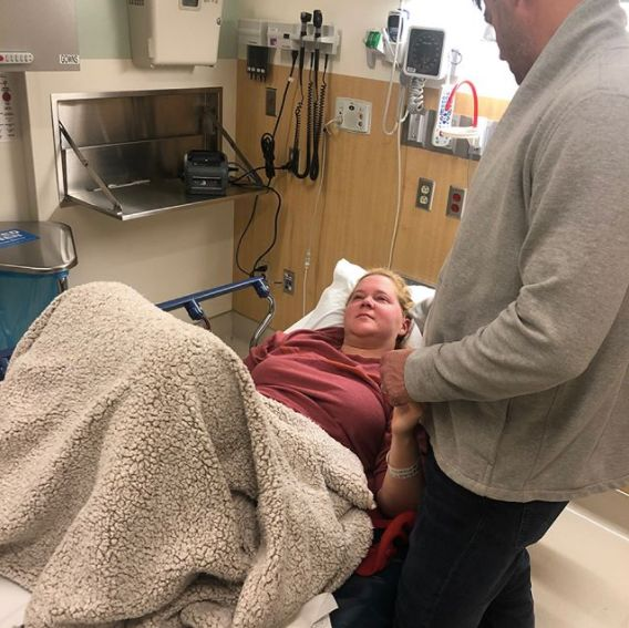 Chris Fischer holds Amy Schumer's hand while she's in the hospital.