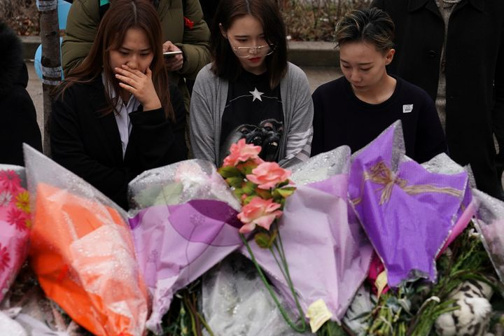 People pay their respects at a makeshift memorial on Toronto's Yonge Street on April 25, two days after the van attack that k