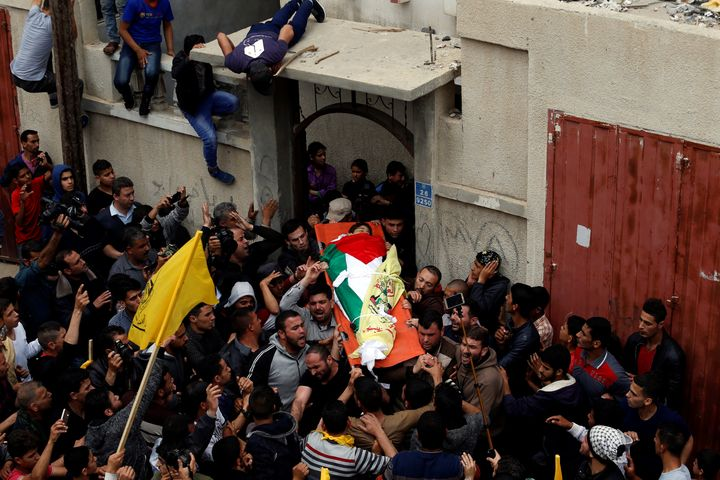 Mourners carry the body of Palestinian Azam Ewidah,15, who was killed at the Israel-Gaza border, during his funeral in the so