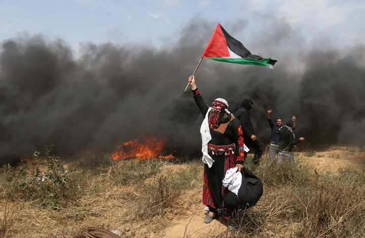 A woman demonstrator holds a Palestinian flag during clashes with Israeli troops at a protest where Palestinians demand the r