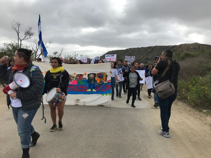 A group of several dozen immigrant rights activists and legal observers march toward the U.S.-Mexico border in San Diego on A