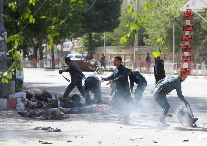 Police officers help journalists who were injured in the second Kabul blast on Monday, April 30, 2018.