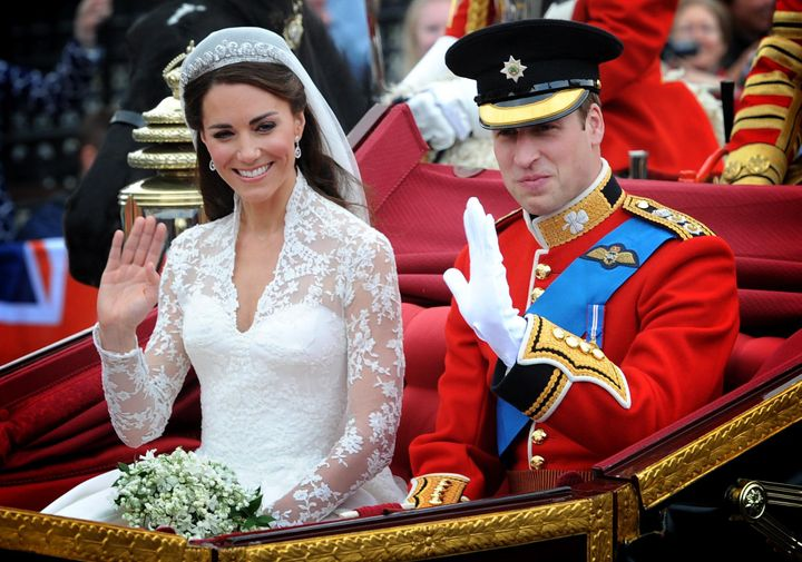 Prince William and the former Kate Middleton wave on the way to their wedding reception.