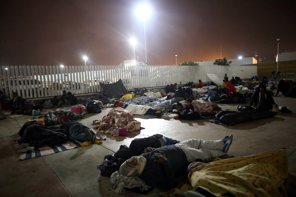Members of a caravan of migrants from Central America sleep near the San Ysidro checkpoint along the United States border.