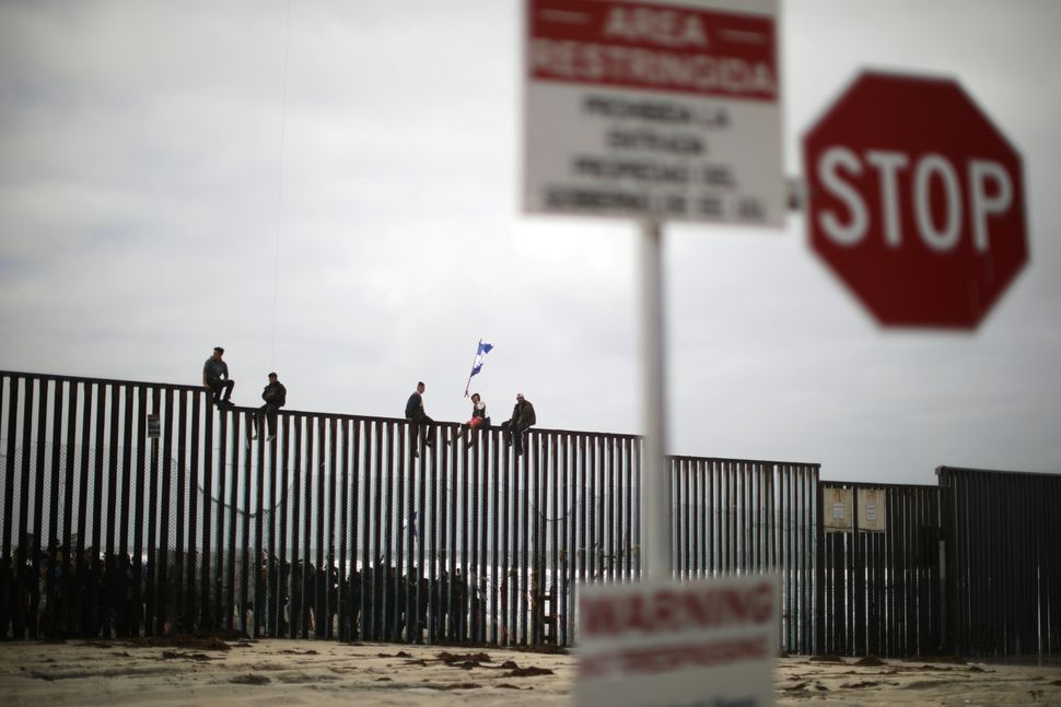 People sit on the top of the U.S.-Mexico border wall.