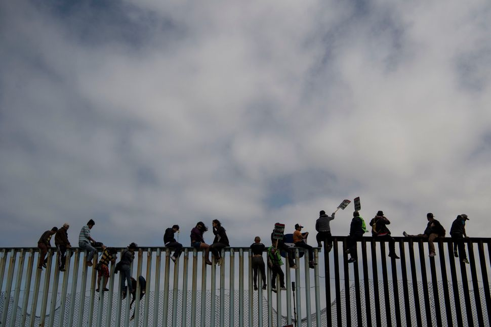 People sit on top of the border wall during the March Without Borders at Friendship Park.