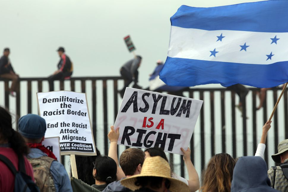 Pro-migrant caravan demonstrators, including a woman waving a Honduran flag, rally as some people climb the border wall.