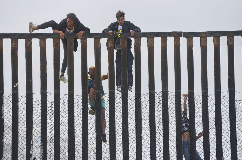 Migrant caravan demonstrators climb the U.S.-Mexico border fence during a rally.