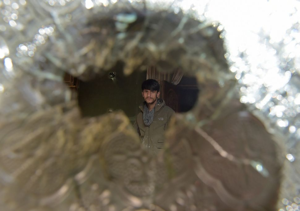 A man is seen through a broken glass at the Kabul house of a parliament member, Mir Wali, on Dec. 22, 2016. Eight people