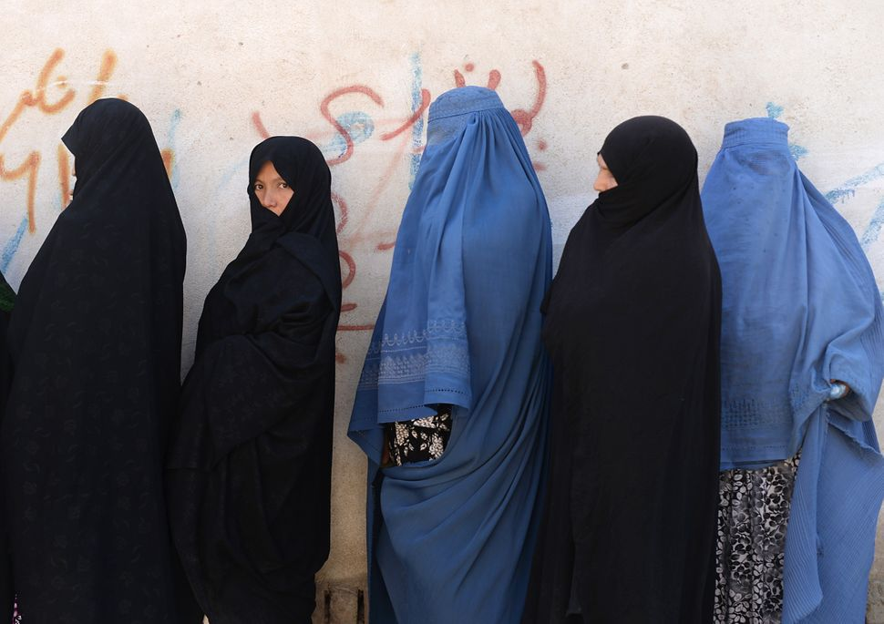 Voters line up at a polling station in Kabul on June 14, 2014.