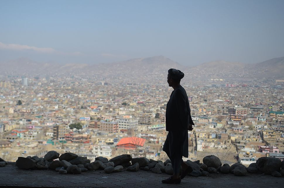 A man walks on a hillside path overlooking Kabul on March 21, 2018, the first day of Nowruz, or Persian New Year,