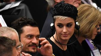 US singer Katheryn Elizabeth Hudson, known professionally as Katy Perry (C) looks towards British actor Orlando Bloom (L) as an unseen Pope Francis delivers a speech to participants at 'Unite To Cure, A Global Health Care Initiative, during his audience at Aula Paolo VI in The Vatican on April 28, 2018. (Photo by Andreas SOLARO / AFP)        (Photo credit should read ANDREAS SOLARO/AFP/Getty Images)