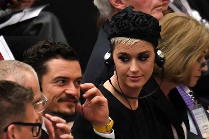 Katy Perry looks toward British actor Orlando Bloom as they listen via headphones to a translation of Pope Francis' spee