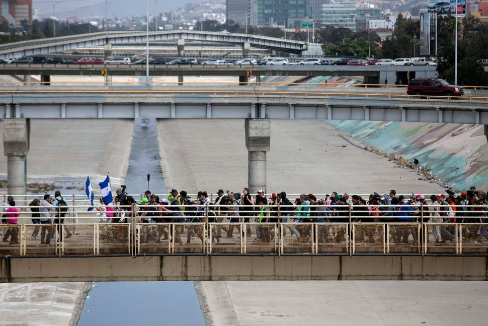 Central American migrants walk to El Chaparral border crossing.