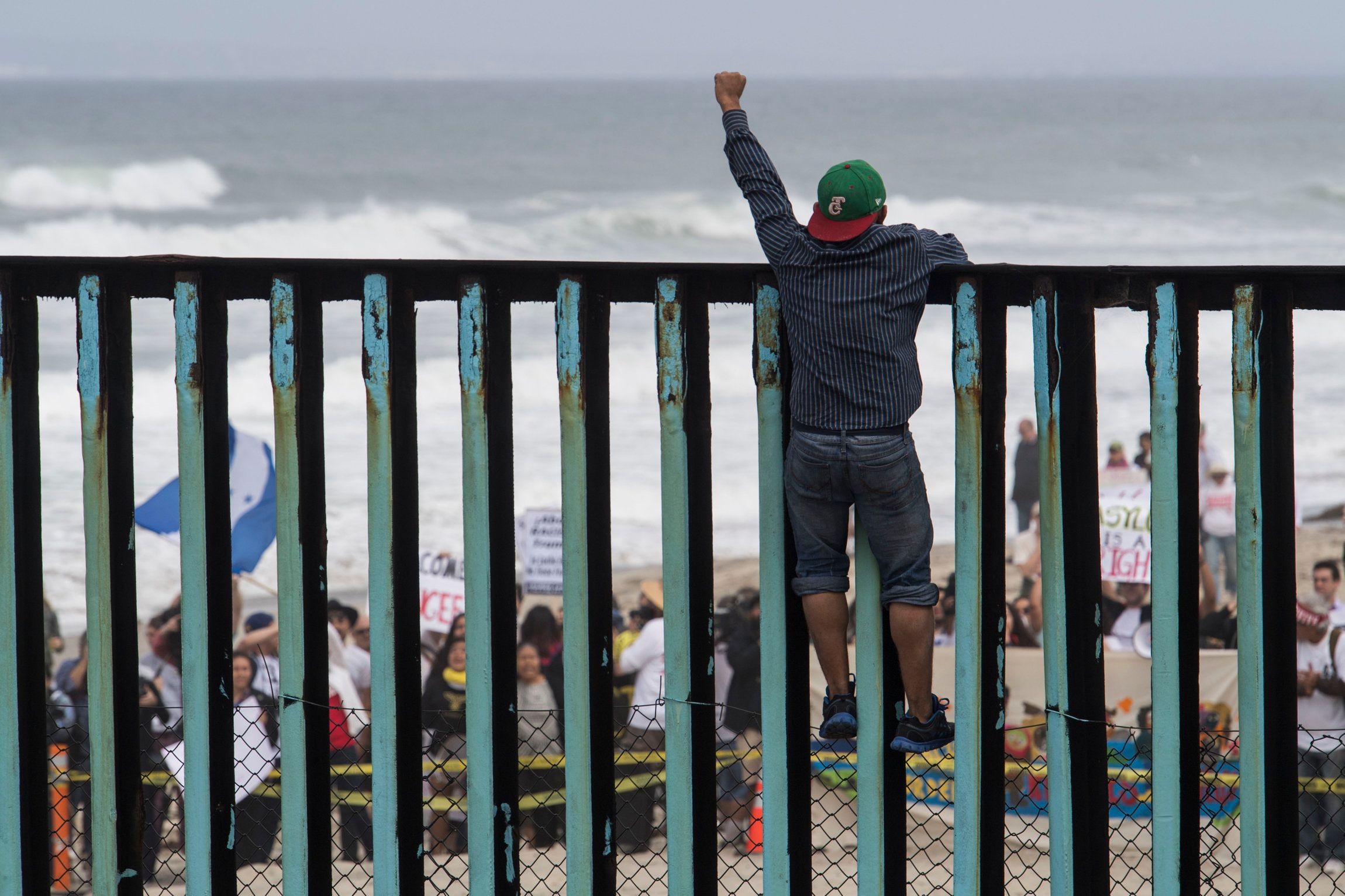 TIJUANA, MEXICO - APRIL 29: A man stands at the top of the border wall and yells to the march on the other side during the March Without Borders at Friendship Park on April 29, 2018 in Tijuana, Mexico. Hundreds of migrants from Central America traveled for about a month across Mexico to reach the United States border. On Sunday the group plans to go to the San Ysidro border crossing south of San Diego, California, where many of the migrants will seek asylum. (Photo by Carolyn Van Houten/The Washington Post via Getty Images)