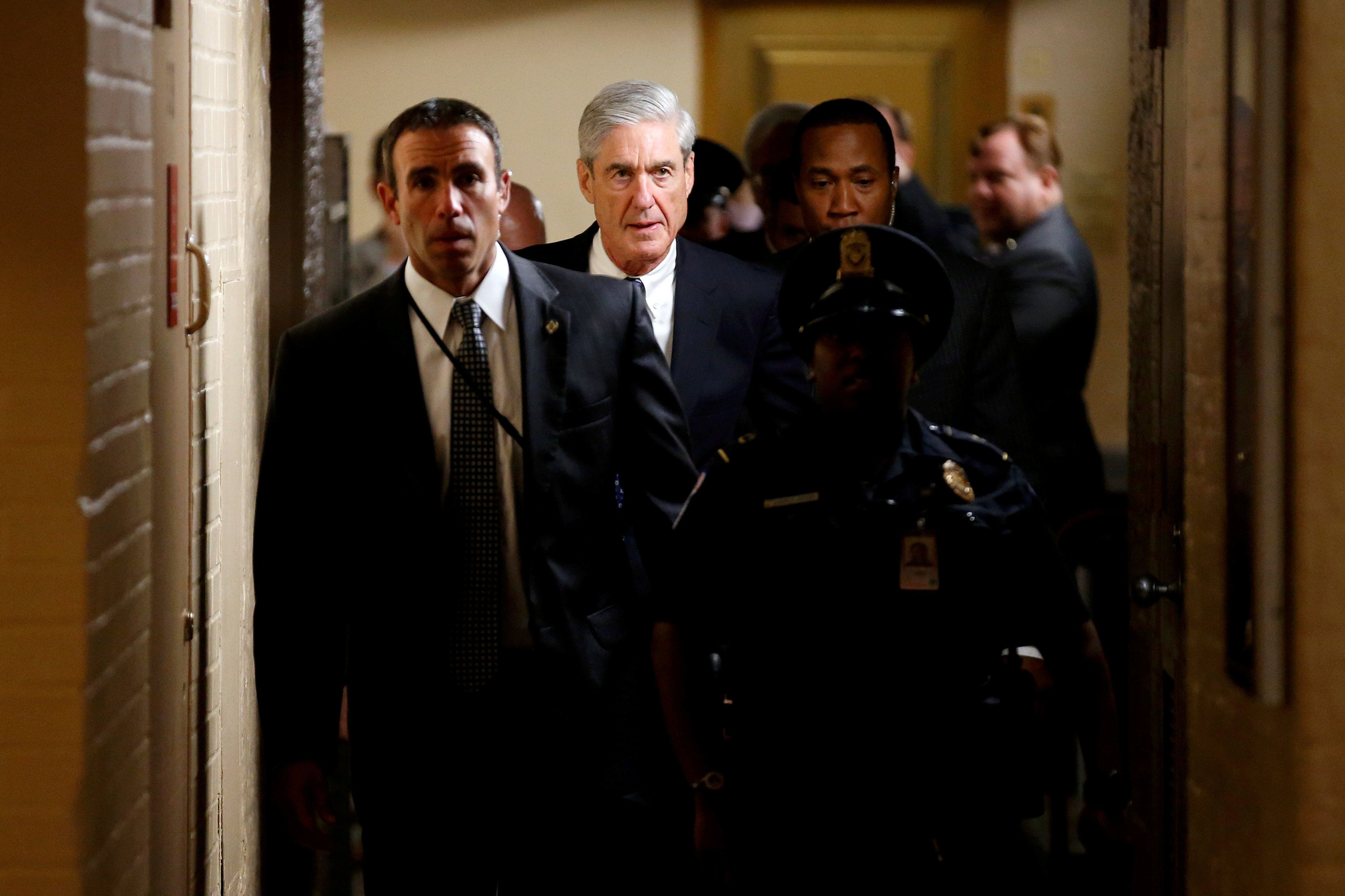 Special counsel Robert Mueller is surrounded by police and security after briefing members of the Senate on his Russia