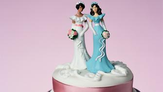 Top tier of wedding cake decorated with two model brides, close-up