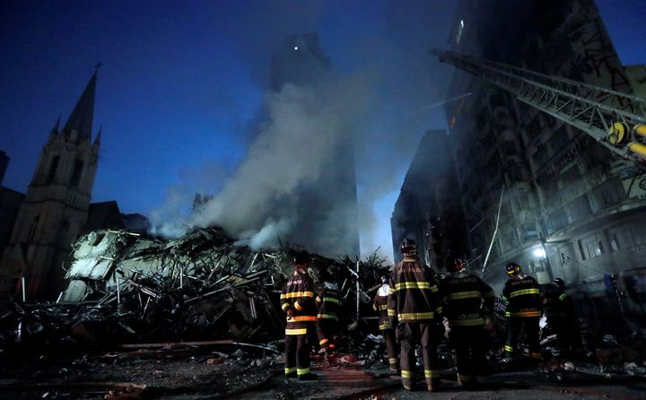 Firefighters stand by outside a site of building collapsed in downtown Sao Paulo, Brazil, May 1.