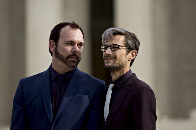 David Mullins (left) and husband Charlie Craig wait to speak to supporters after U.S. Supreme Court arguments...