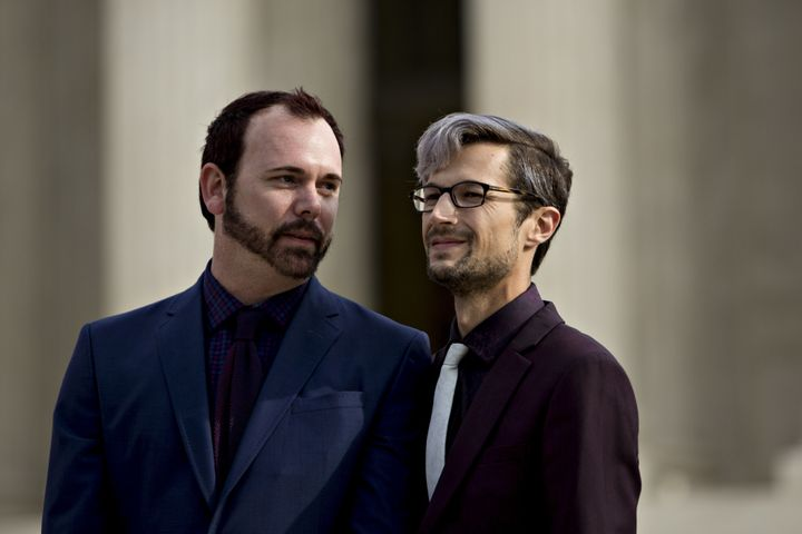 David Mullins (left) and husband Charlie Craig wait to speak to supporters after U.S. Supreme Court arguments in the Masterpi
