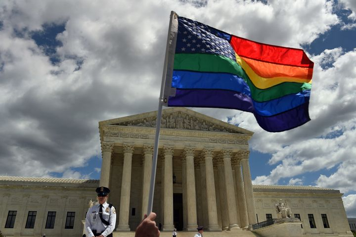 A supporter of gay marriage waves his rainbow flag in front of the U.S. Supreme Court in Washington, D.C., April 28, 20