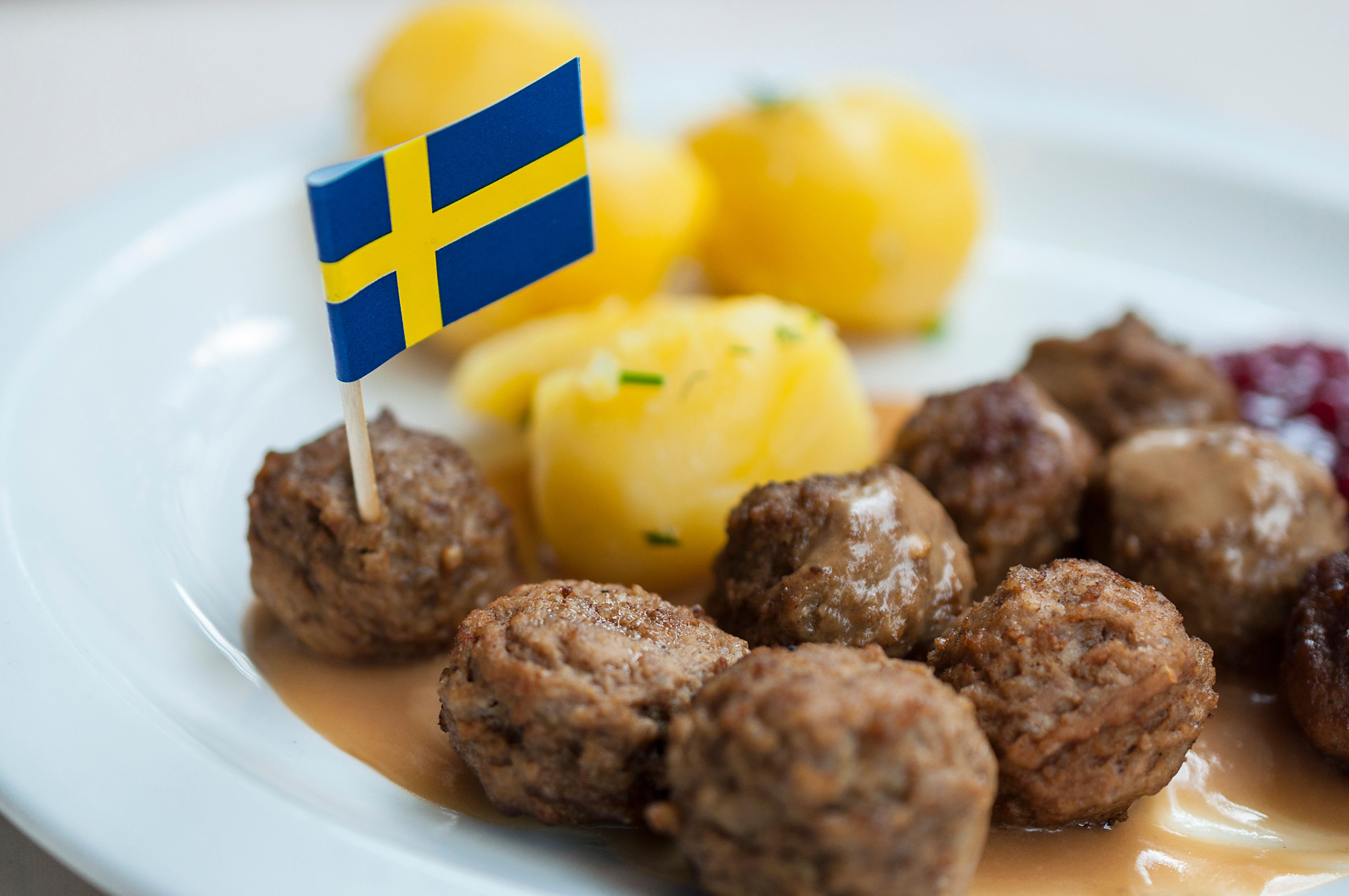 Meatballs with boiled potatoes and sweet red sauce decorated by Swedish flag - traditional Swedish dish