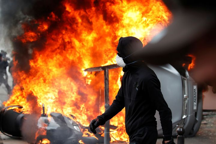 A masked demonstrator walks near a car that burns outside a Renault automobile garage in Paris during May Day protests.