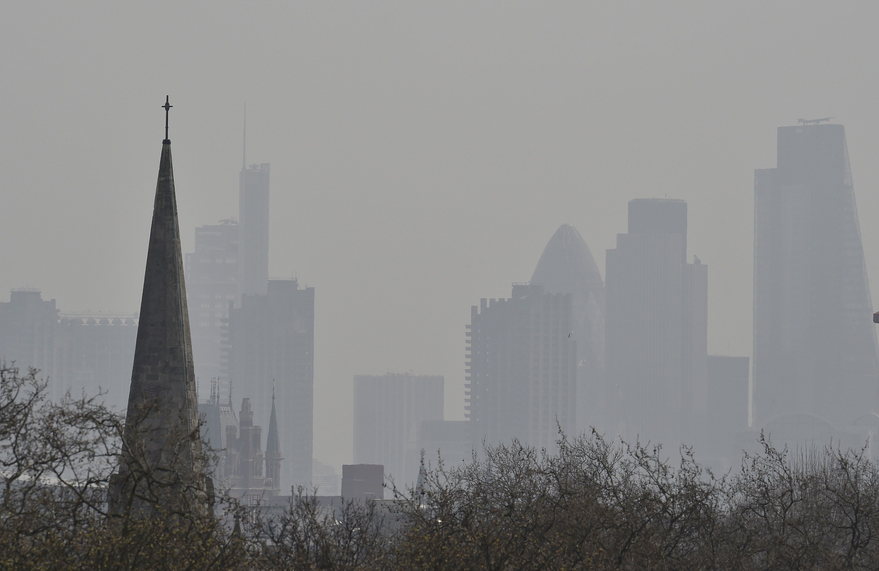 The City of London financial district is seen from Primrose Hill as high air pollution obscures the skyline...