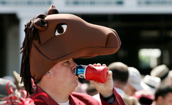 A race fan drinks a beer as he wears a horse hatbefore the 2008 derby.