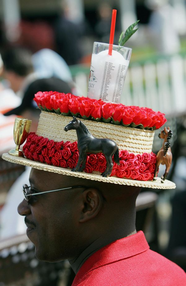 The classic mint julep glasssits atop a derby hat worn by a race fan in 2005.