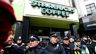 Police officer protect a Starbucks after demonstrators threatened to occupy it during a protest march organised by the Trades Union Congress (TUC), in Oxford Street, in central London October 20, 2012. Thousands of British protesters marched through central London on Saturday against public spending cuts and tax rises enacted by a government fighting accusations it is run by an upper-class elite that ignores the plight of recession-hit voters.      REUTERS/Suzanne Plunkett (BRITAIN - Tags: BUSINESS POLITICS EMPLOYMENT)