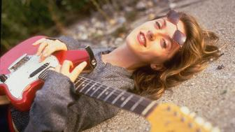 Alternative rock star Liz Phair strumming on guitar as she lies on ground outdoors.  (Photo by Tom Maday/The LIFE Images Collection/Getty Images)