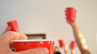 People toasting using red party cups.