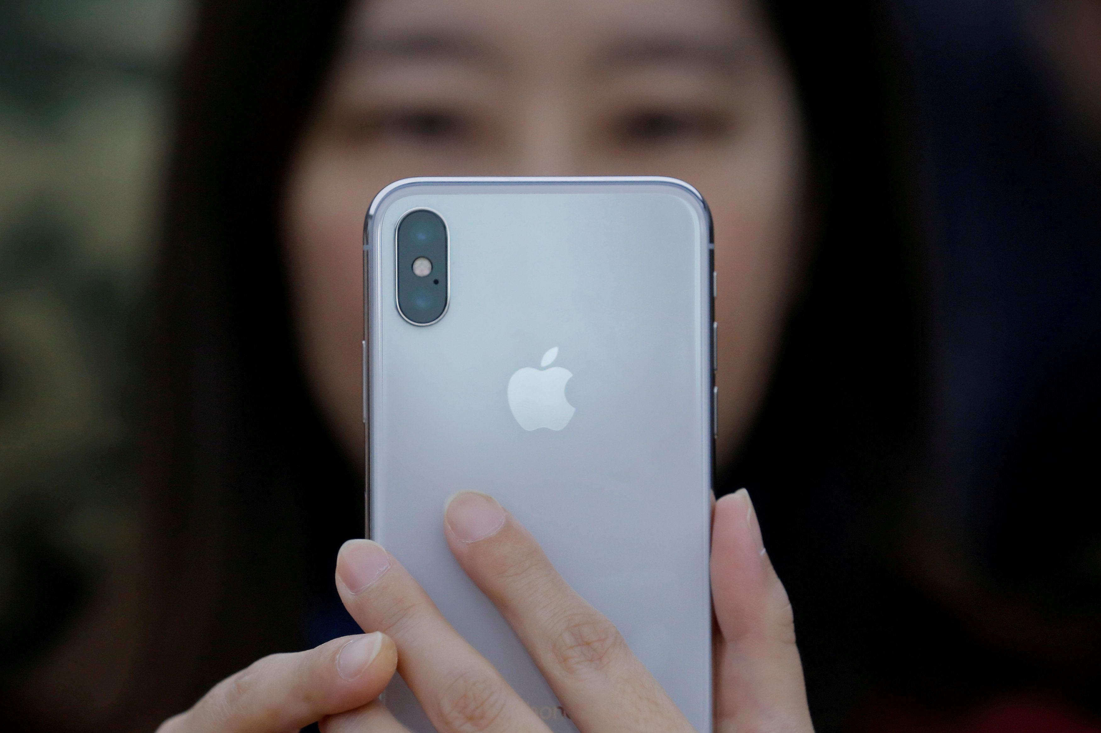 A attendee uses a new iPhone X during a presentation for the media in Beijing, China October 31, 2017. REUTERS/Thomas Peter