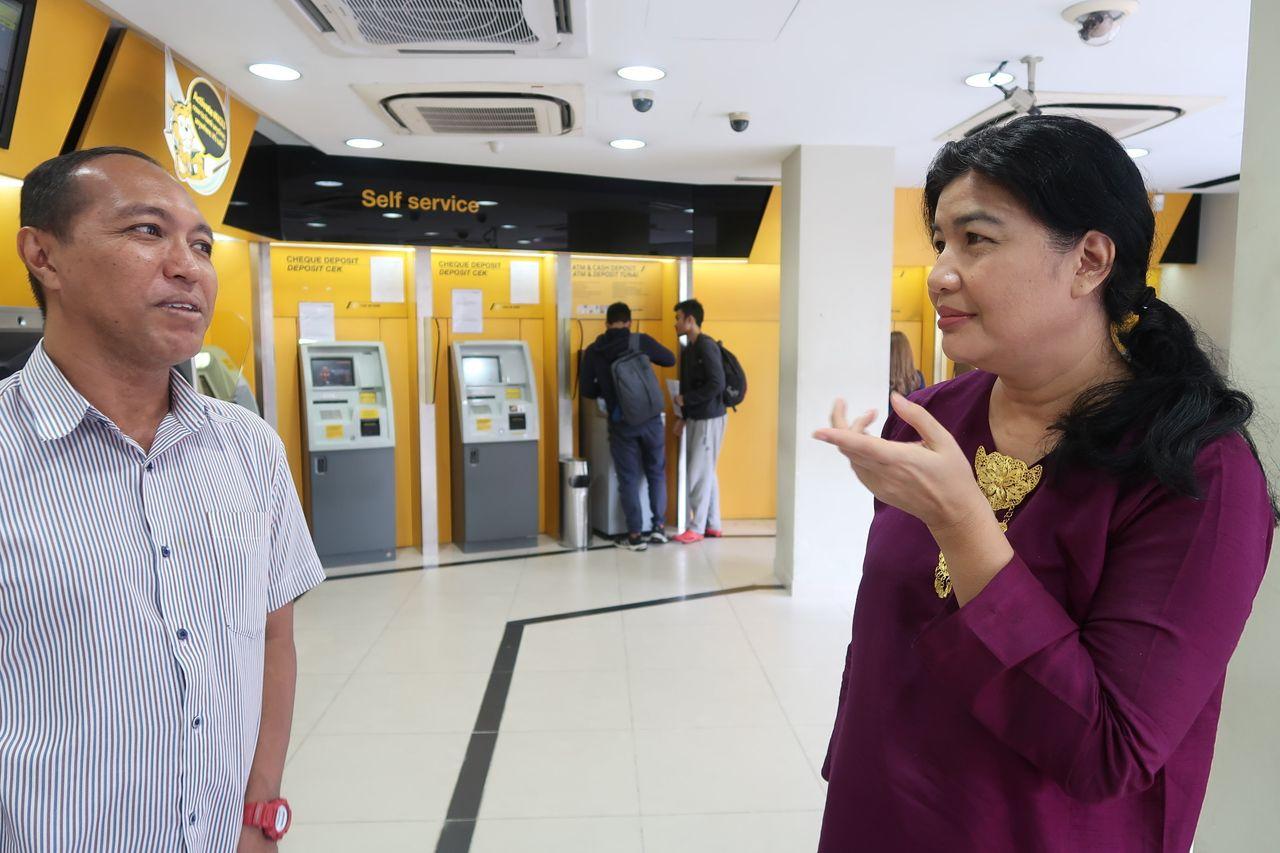 Alzari Mahshar (left) and Tengku Elida Bustaman are volunteers for a fundraising organization to help people vote.