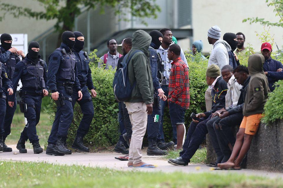 Polizisten kontrollieren Flüchtlinge vor der