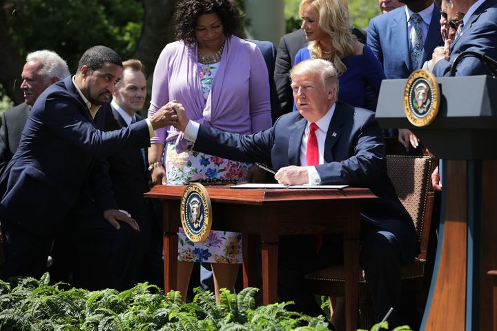 Pastor Darrell Scott and President Donald Trump shake hands at the the National Day of Prayer ceremony in the White House Ros