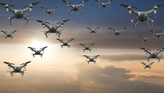 A flock of drones flying in the sky against a terrific sunset