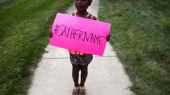 LISLE, IL  - JULY 25: Daija Belcher, 5, holds a sign in front of the DuPage African Methodist Episcopal Church during the funeral service for Sandra Bland on July 25, 2015 in Lisle, Illinois. Bland's death roused suspicion nationwide after the 28-year-old was found hanging from a plastic bag three days after she was pulled over by a Texas State Trooper for a traffic violation. (Photo by Jonathan Gibby/Getty Images)