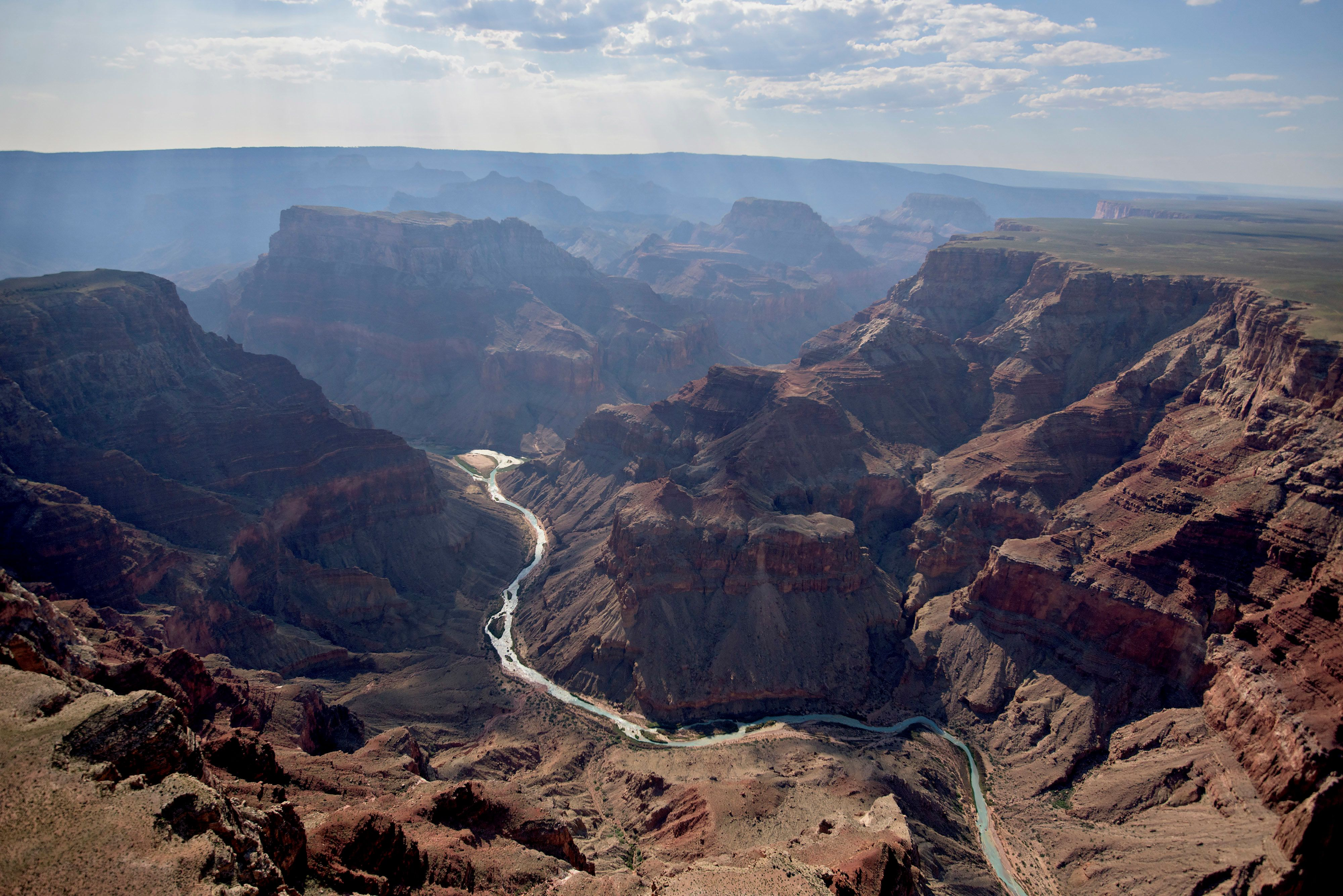 The confluence of the Little Colorado River, foreground, and the Colorado River is seen in Grand Canyon National Park in this aerial photograph taken above Grand Canyon, Arizona, U.S., on Thursday, June 25, 2015. Developers Confluence Partners have proposed a 420-acre development along the canyon's rim. The Grand Canyon has seen a 20 percent increase in visitation through the first quarter of this year, according to a park spokesperson. Photographer: Daniel Acker/Bloomberg via Getty Images