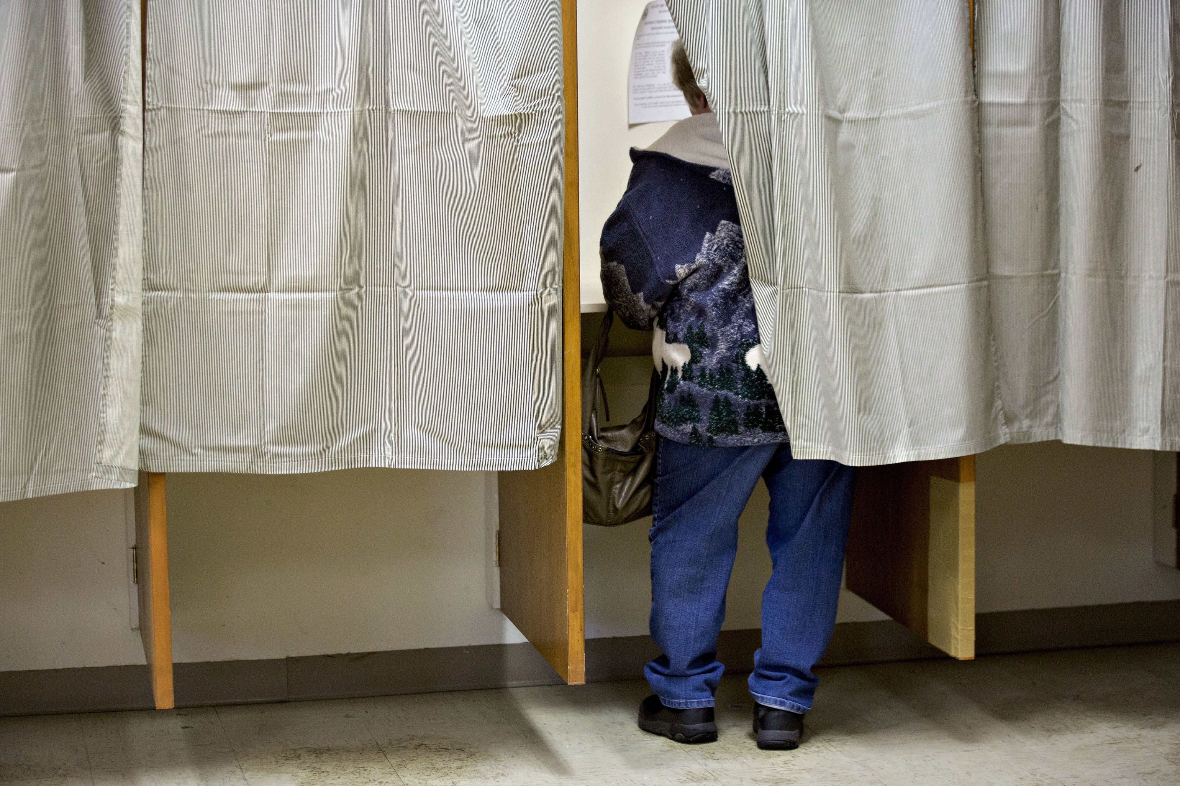 A resident stands in a voting booth while marking her ballot at the Bartlett town hall during the first-in-the-nation New Hampshire presidential primary in Bartlett, New Hampshire, U.S., on Tuesday, Feb. 9, 2016. Polls suggest that Donald Trump maintains a dominant lead against his Republican rivals in New Hampshire ahead of today's primary. Photographer: Andrew Harrer/Bloomberg via Getty Images